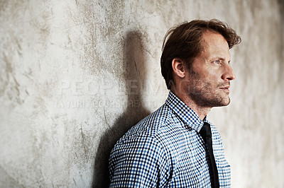 Buy stock photo Studio shot of a thoughtful looking businessman leaning against a wall