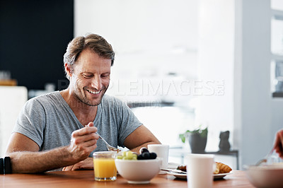 Buy stock photo Shot of a man eating breakfast at the dining table