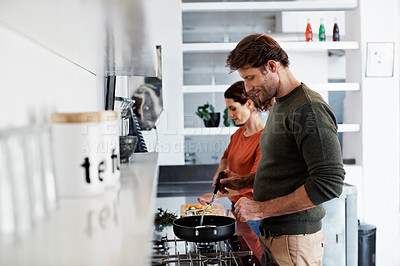 Buy stock photo Shot of a smiling mature couple cooking together in their kitchen
