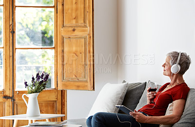 Buy stock photo Shot of a mature woman sitting on her sofa listening to music on a digital tablet and drinking wine