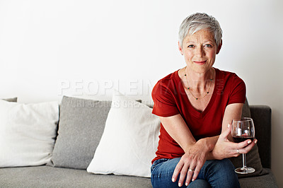 Buy stock photo Portrait of a smiling mature woman drinking wine in her living room