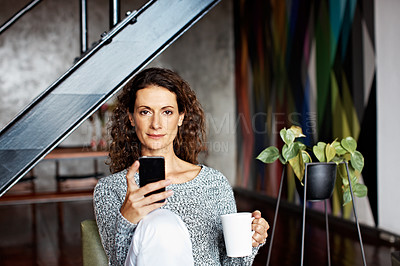 Buy stock photo Portrait of a mature woman using her cellphone while sitting on a chair in her living room