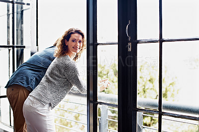 Buy stock photo Shot of a mature couple leaning on their balcony railing looking outside