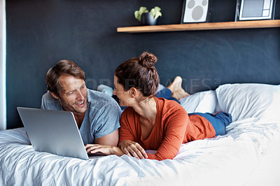 Buy stock photo Shot of a mature couple lying on their bed using a laptop
