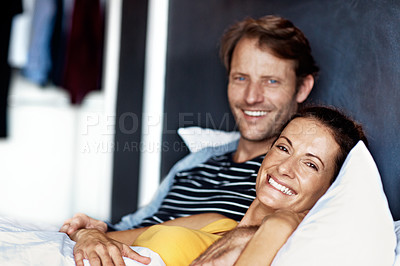 Buy stock photo Portrait of a content mature couple lying in bed together