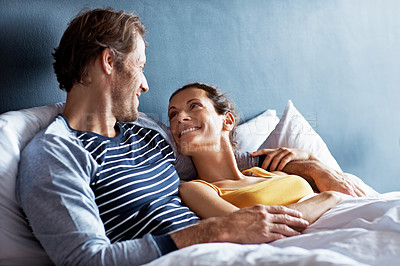 Buy stock photo Shot of a content mature couple lying in bed together
