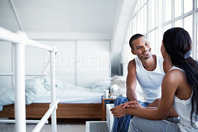 Buy stock photo Shot of a young couple talking together while sitting in their bedroom