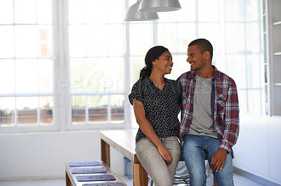 Buy stock photo Shot of a happy couple leaning on their dining table