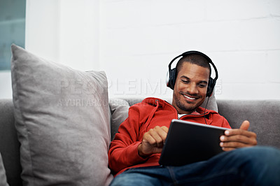 Buy stock photo Shot of a young man wearing headphones while using a digital tablet