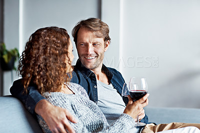 Buy stock photo Shot of a smiling mature couple drinking wine while sitting on a sofa in their living room