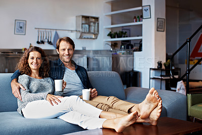 Buy stock photo Portrait of a content mature couple sitting on their living room sofa drinking coffee
