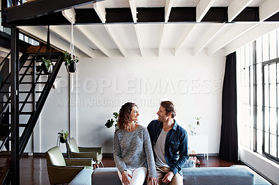 Buy stock photo Shot of a content mature couple leaning on a sofa in their living room