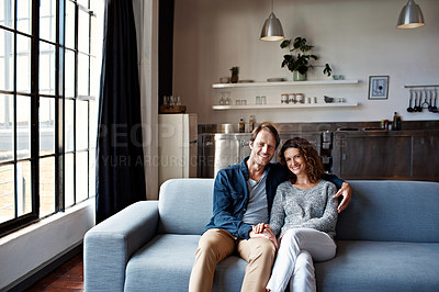 Buy stock photo Portrait of a content mature couple sitting on their living room sofa