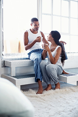 Buy stock photo Shot of a young couple talking together and drinking coffee while sitting in their bedroom