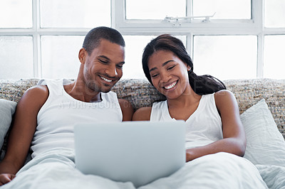 Buy stock photo Shot of a young couple lying in bed using a laptop