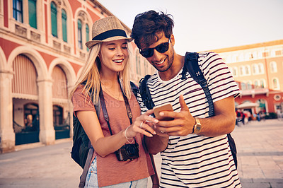 Buy stock photo Shot of a young couple looking at something on a phone while touring a foreign city