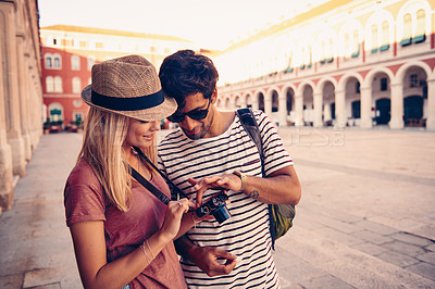 Buy stock photo Shot of a young couple looking at the pictures they took while touring a foreign country