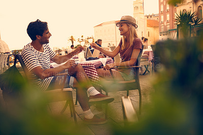 Buy stock photo Shot of a young couple having a glass of wine after a long day of touring