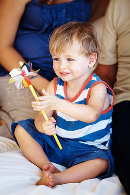 Buy stock photo Young smiling kid sitting with family and holding hand windmill