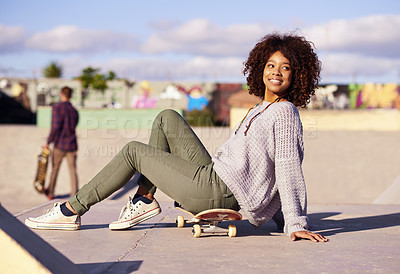 Buy stock photo Shot of a young woman sitting on her skateboard in a skatepark
