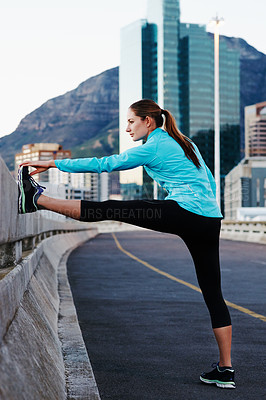 Buy stock photo Shot of a young woman stretching before a run in the city