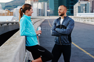 Buy stock photo Shot of a young couple out for a run in the city