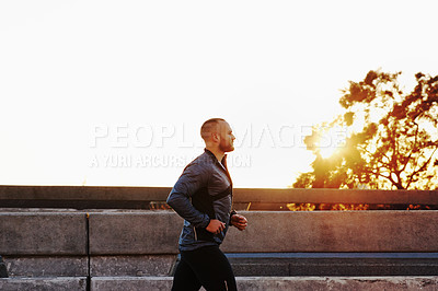 Buy stock photo Shot of a man out for a run in the city
