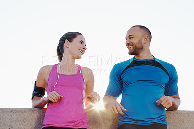 Buy stock photo Shot of an athletic couple taking a break running in the city