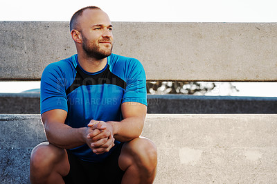Buy stock photo Cropped shot of an athletic man taking a break from his run in the city