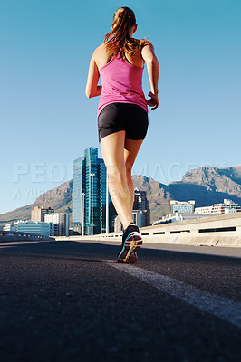 Buy stock photo Rearview shot of an athletic woman running in the city