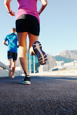 Buy stock photo Rearview shot of an athletic couple running in the city