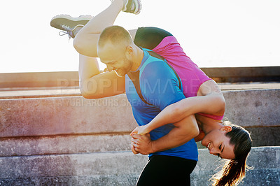 Buy stock photo Cropped shot of an athletic couple messing around while running in the city