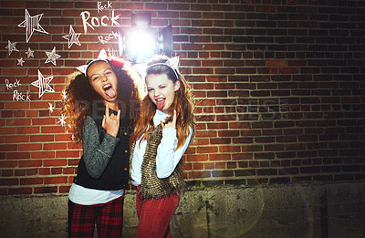 Buy stock photo Shot of two girls pulling faces and making a rock gesture