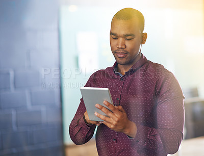 Buy stock photo Shot of a male designer using a digital tablet in the office