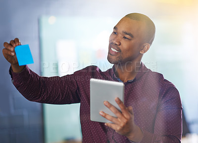 Buy stock photo Shot of a male designer holding a tablet looking at sticky notes on a glass wall