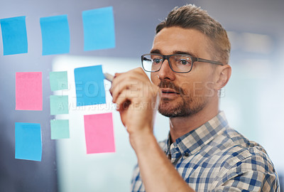 Buy stock photo Shot of a male designer writing on sticky notes stuck a glass wall
