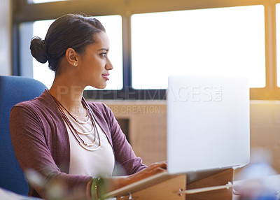 Buy stock photo Shot of a young businesswoman working on her laptop in the office
