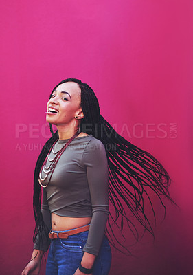 Buy stock photo Shot of an attractive young woman with braids posing against a pink background