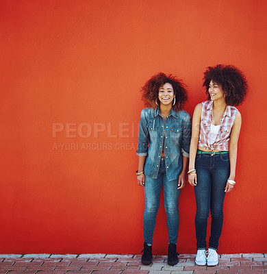 Buy stock photo Shot of two young friends posing in front of a red wall