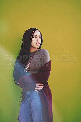 Buy stock photo Shot of an attractive young woman posing against a green wall