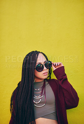 Buy stock photo Shot of a young woman wearing sunglasses against a green background
