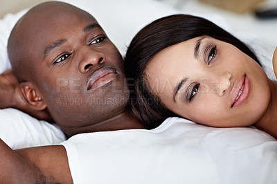 Buy stock photo Shot of a pensive looking young couple lying in bed together