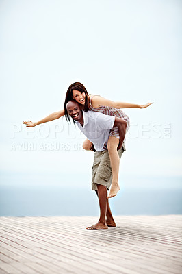 Buy stock photo Shot of a man giving his wife a piggyback while walking on a promenade