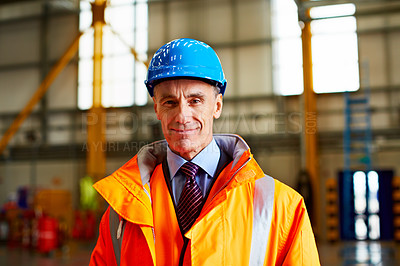 Buy stock photo Portrait of a mature man in workwear standing in a large industrial building