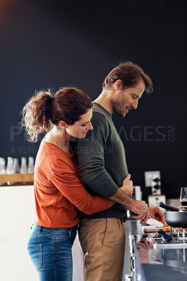 Buy stock photo Shot of an affectionate mature couple cooking together in their kitchen
