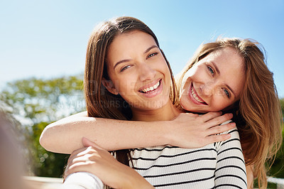 Buy stock photo Selfie of two young friends hugging while enjoying a day outside together