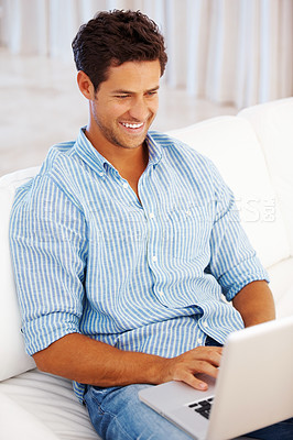 Buy stock photo Man sitting on a sofa at home using laptop and smiling