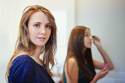 Buy stock photo Shot of two young woman putting on makeup in a bathroom