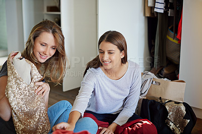 Buy stock photo Shot of a young woman helping her friend choose a dress to wear