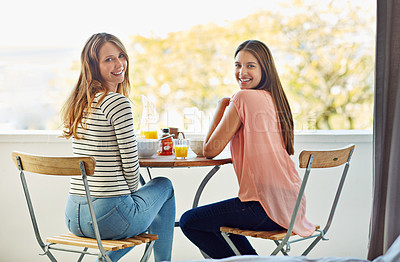 Buy stock photo Portrait of two friends eating breakfast together on a balcony